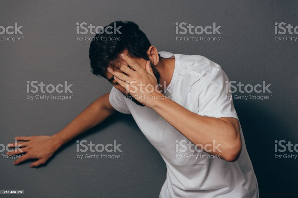 Man suffering from dizziness with difficulty standing up while leaning on wall stock photo