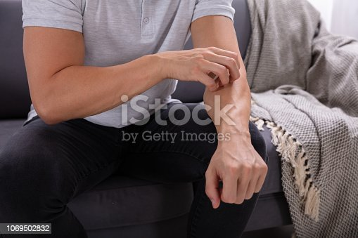 Midsection View Of A Man Sitting On Sofa Suffering From Itching