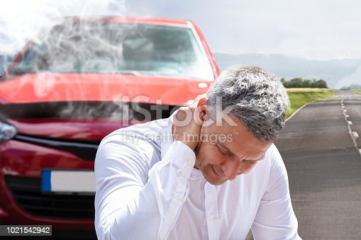 istock Man Suffering From Neck Pain In Front Of Breakdown Car 1021542942