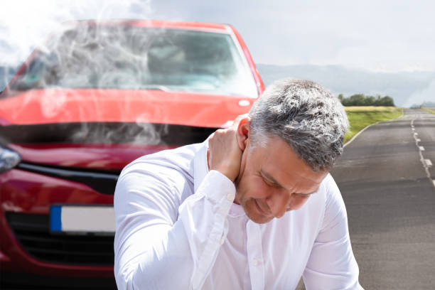 Man Suffering From Neck Pain In Front Of Breakdown Car stock photo