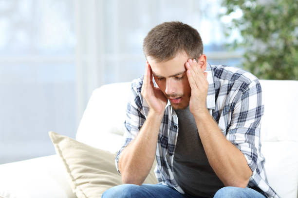 Man suffering headache at home stock photo