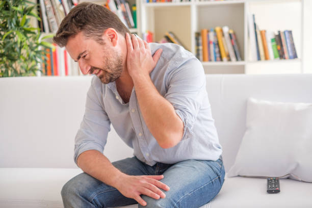 Man suffering neck ache seated on the sofa Man feeling pain to the neck at home after bad posture cervical vertebrae stock pictures, royalty-free photos & images