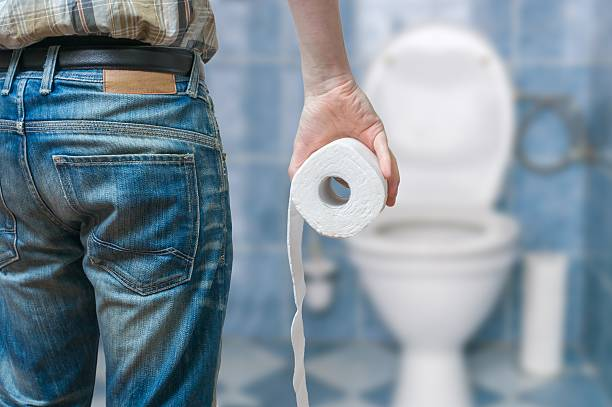 man suffers from diarrhea holds toilet paper roll - constipation stock pictures, royalty-free photos & images