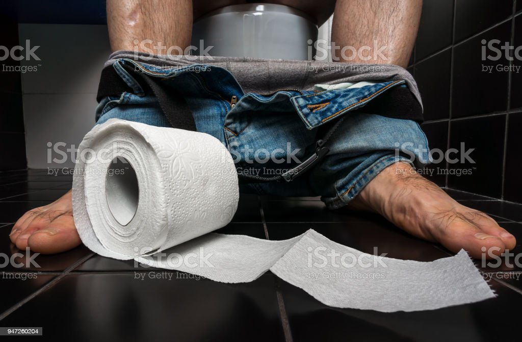 Man suffers from diarrhea is sitting on toilet bowl stock photo