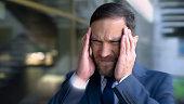 istock Man suffers from headache, massaging temples, migraine dizzy effect, close up 1091529772