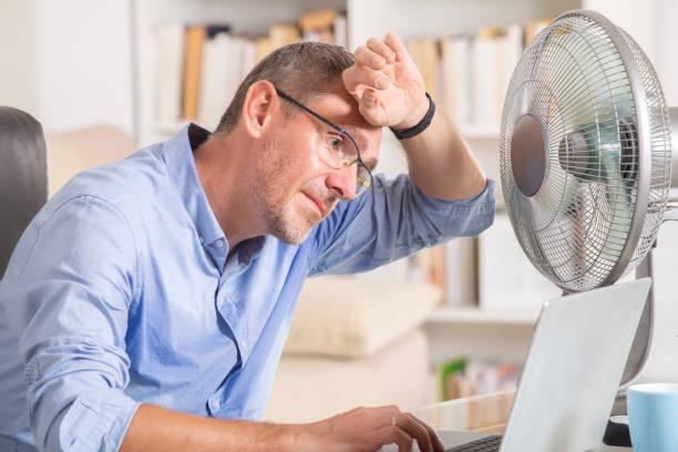 el hombre sufre de calor en la oficina o en casa - calor fotografías e imágenes de stock