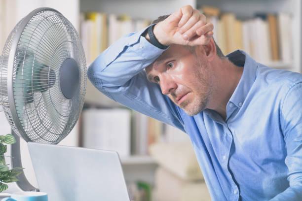 Mann leidet unter Hitze im Büro oder zu Hause – Foto