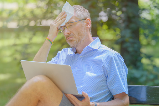 Man suffers from heat while working with laptop