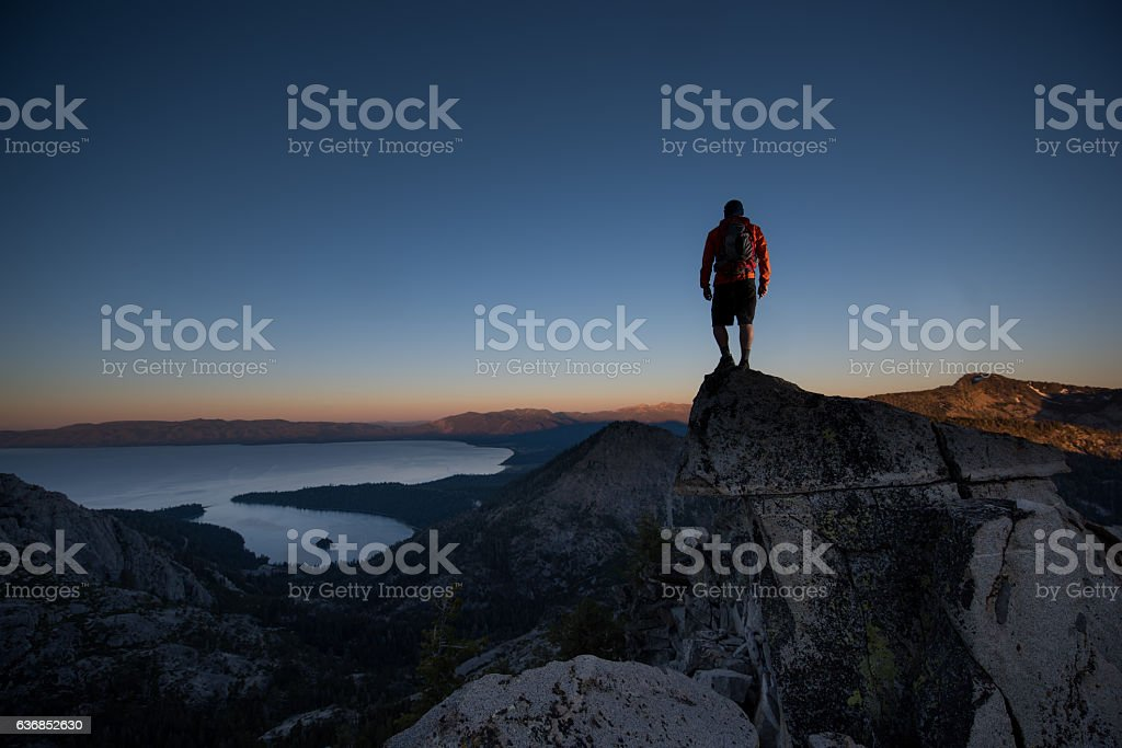 Man summiting a beautiful mountain top in Lake Tahoe stock photo
