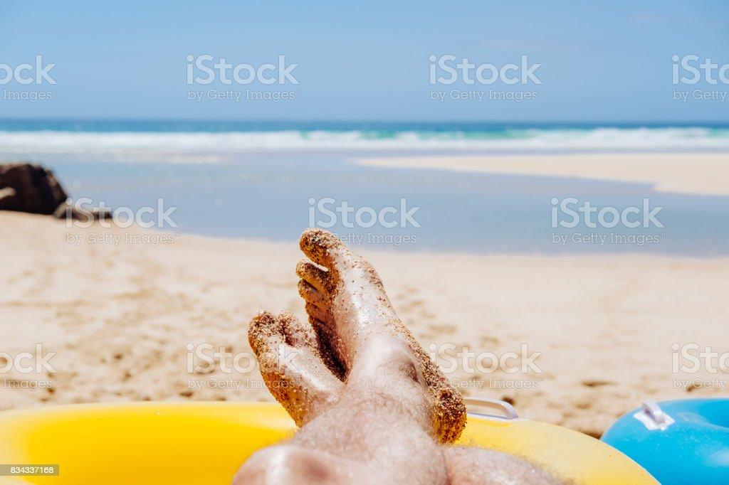 POV man sunbathing, Pedn Vounder beach, Cornwall stock photo