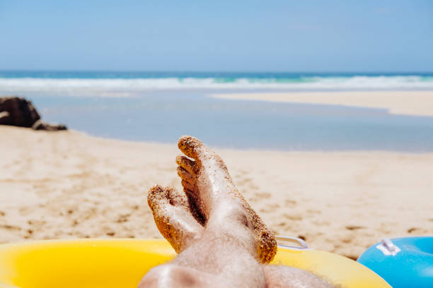 pov man sunbathing, pedn vounder beach, cornwall - rubber ring stock pictures, royalty-free photos & images