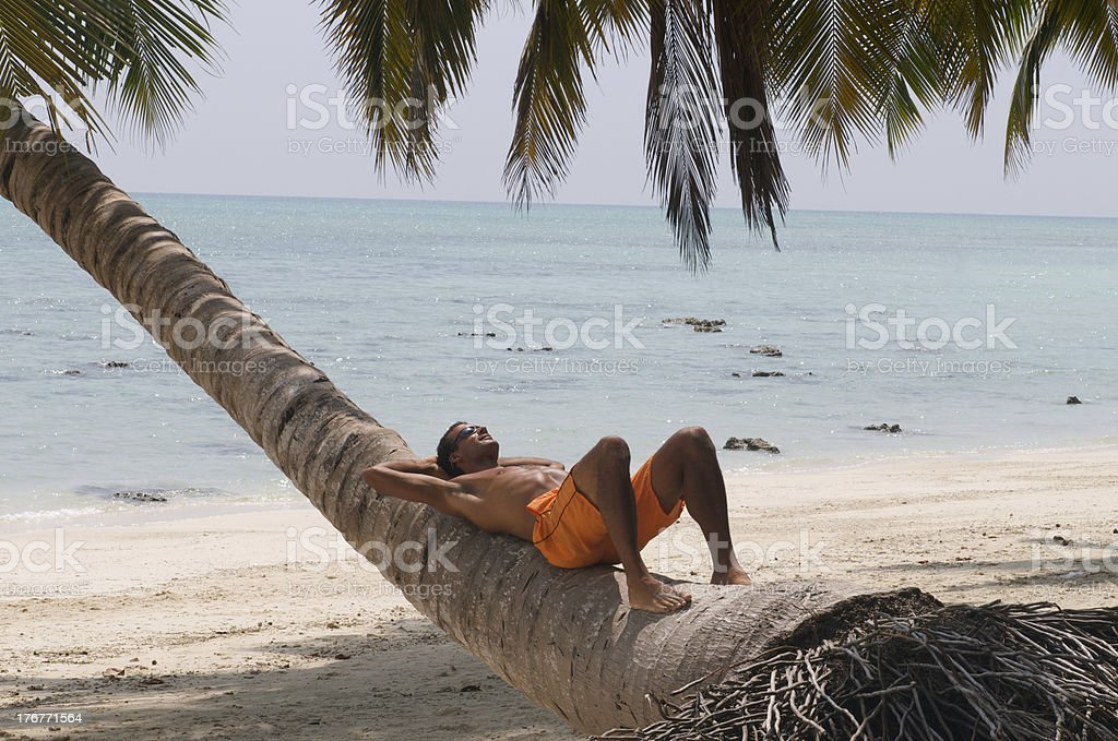 Man sunbathing under tropical palm trees royalty-free stock photo