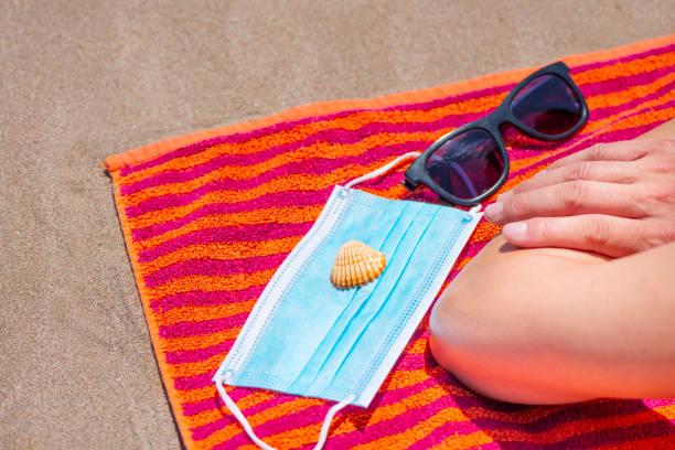 man, sunglasses, seashell and mask on the beach stock photo