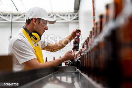 istock Man supervising the operation of a bottling machine 1206641733