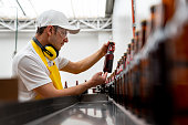 Latin American man supervising the operation of a bottling machine at a brewery - industrial concepts