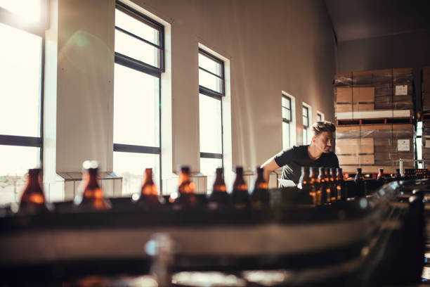 Man supervising the production of craft beer at brewery stock photo