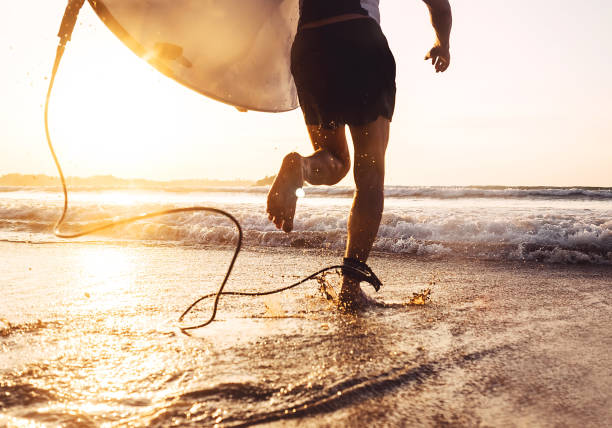 man surfer run in ocean with surfboard. active vacation, health lifestyle and sport concept image - surf foto e immagini stock