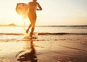 Man surfer run in ocean with surfboard in sunset light