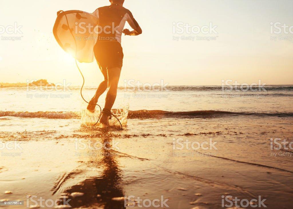 Mann-Surfer mit Surfbrett im Abendlicht im Ozean laufen – Foto