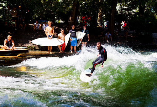 Man surfing at the Eisbach river in Munich Germany