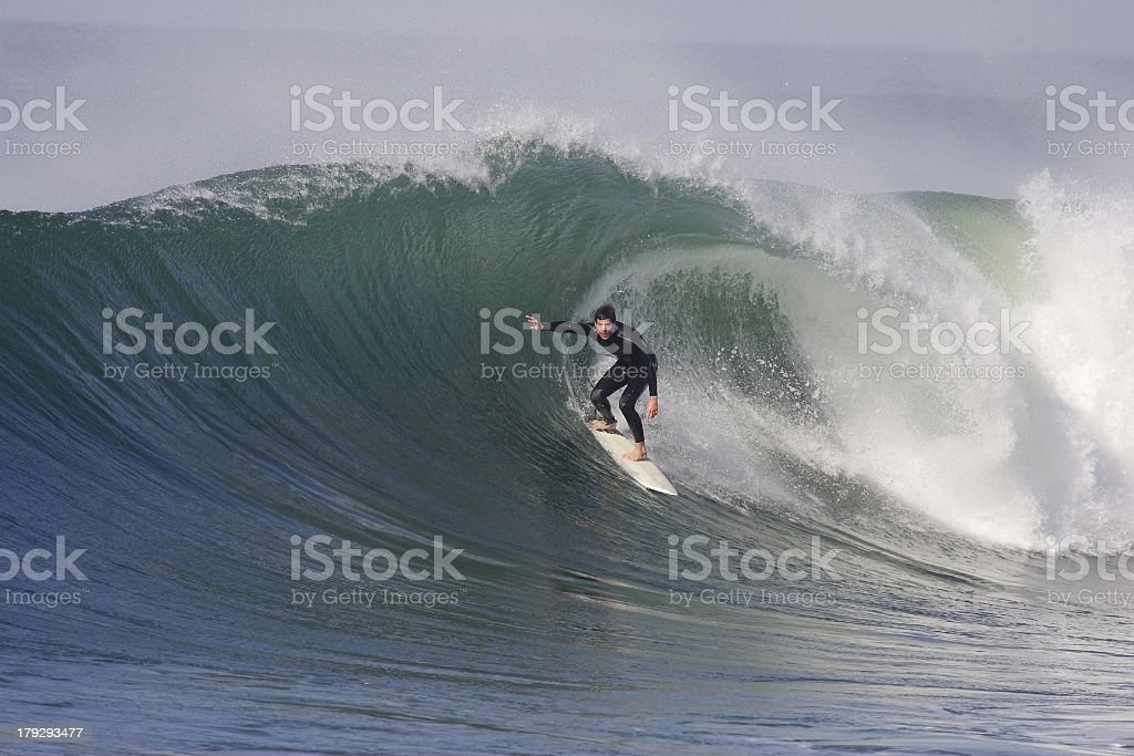 A man surfing on a wave with a surfboard stock photo