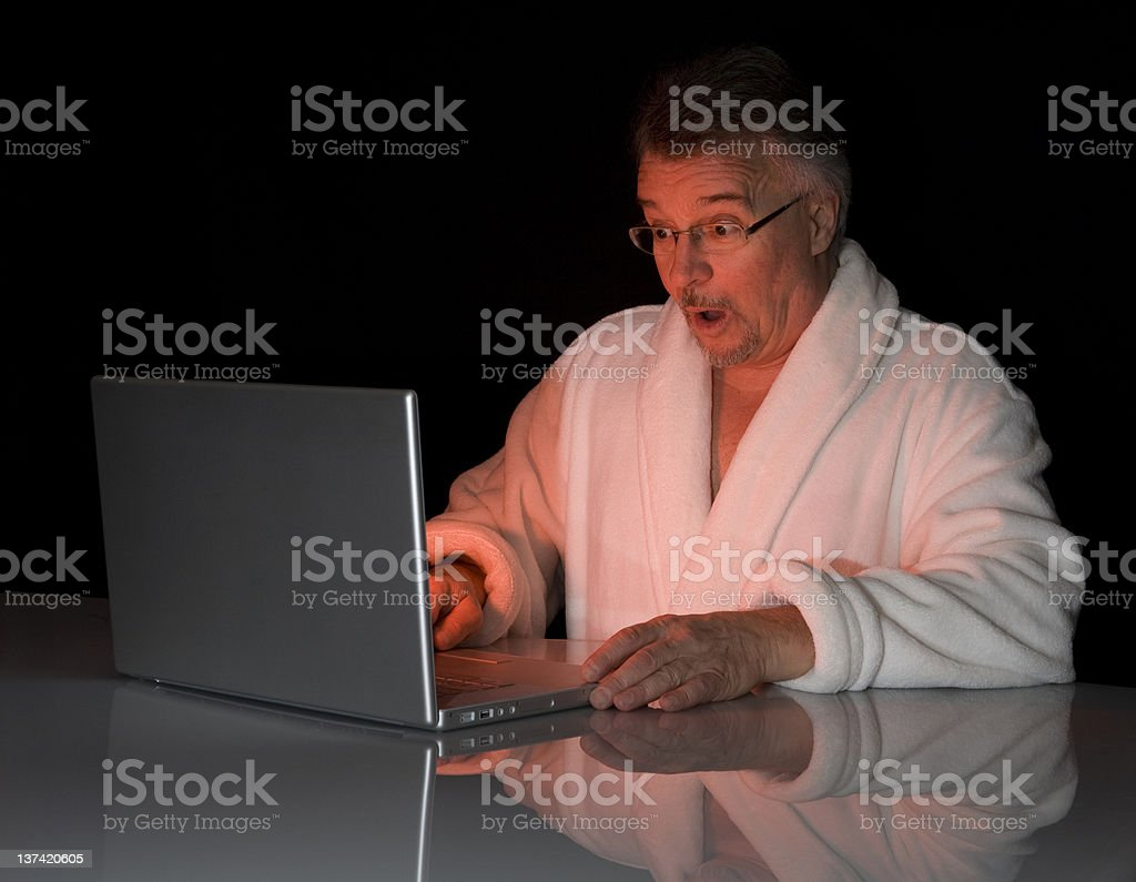 A man surfing the Internet and looking surprised stock photo