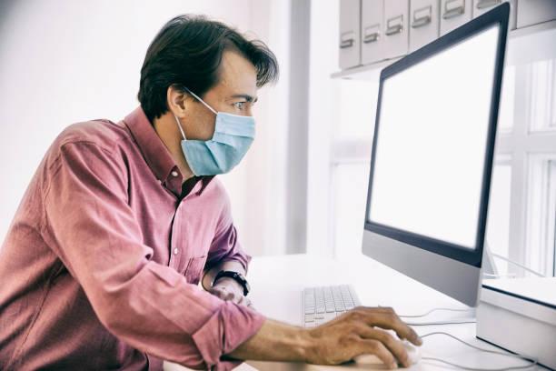 Mann, der mit einer Gesichtsmaske im Internet surft. – Foto