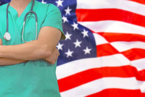 Mann Chirurg oder Arzt mit Stethoskop auf dem Hintergrund der Flagge der Vereinigten Staaten von Amerika. Gesundheitsversorgung, Chirurgie und medizinisches Konzept in den USA. – Foto