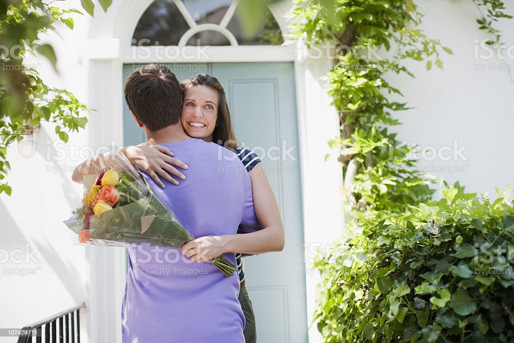 Man surprising girlfriend with bouquet of roses royalty-free stock photo