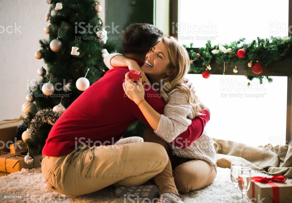 Young man surprising his girlfriend on christmas