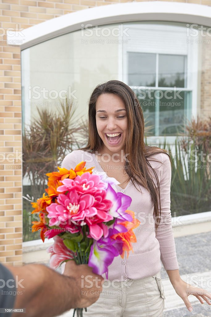 Man surprising his girlfriend with a bouquet royalty-free stock photo