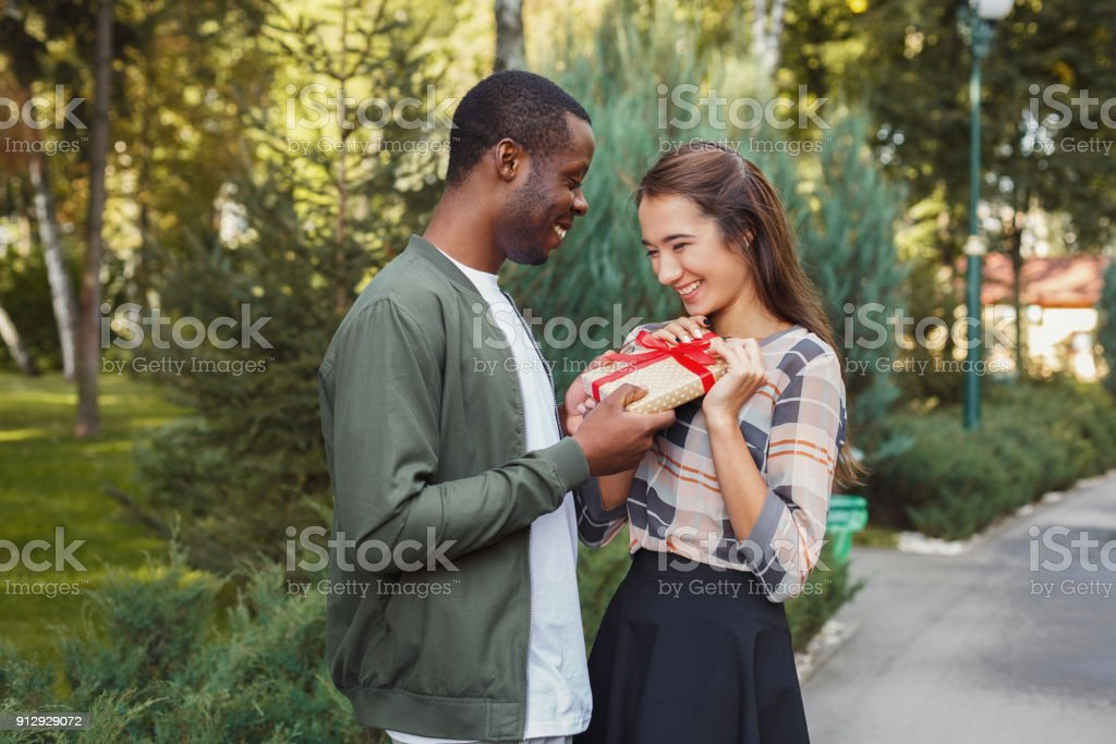 Man surprising his girlfriend with gift stock photo