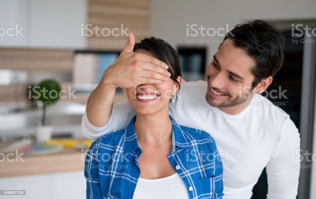 Man surprising woman at home stock photo