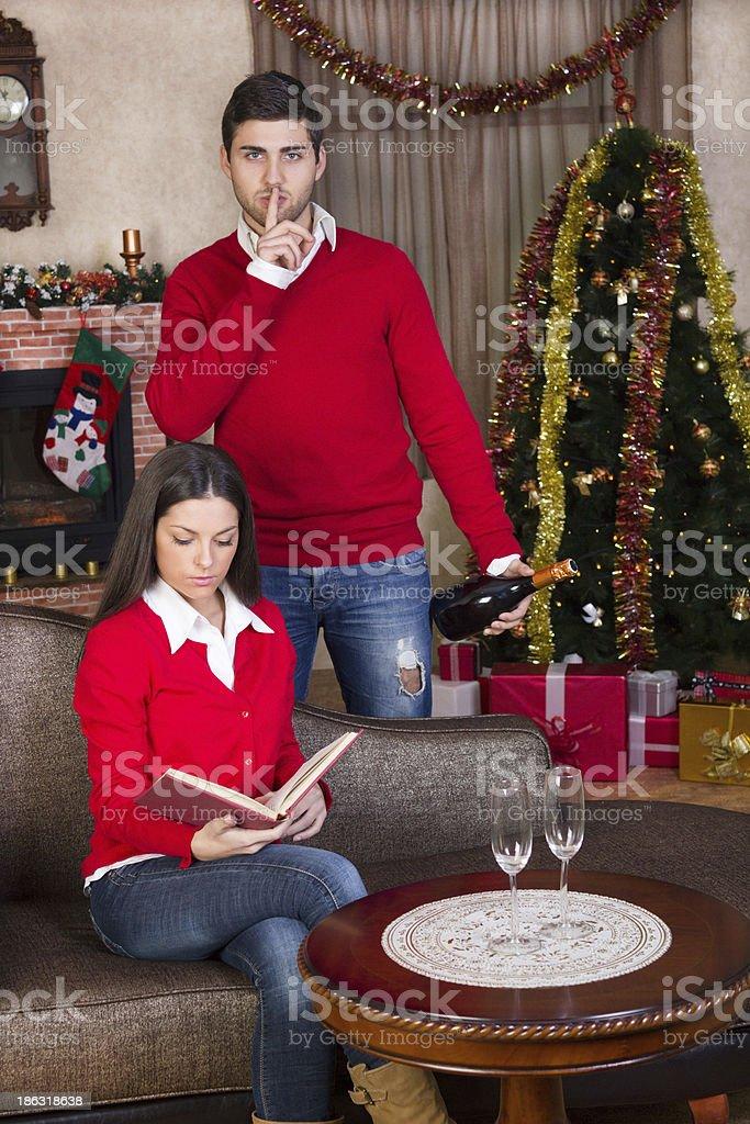 Man surprising woman on Christmas evening royalty-free stock photo