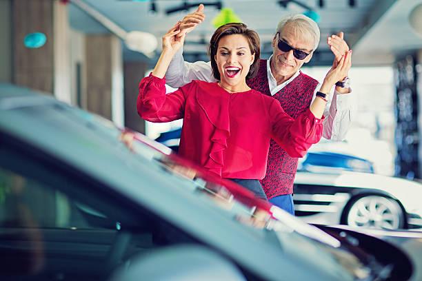 man surprising woman with a new car - homme faire coucou voiture photos et images de collection