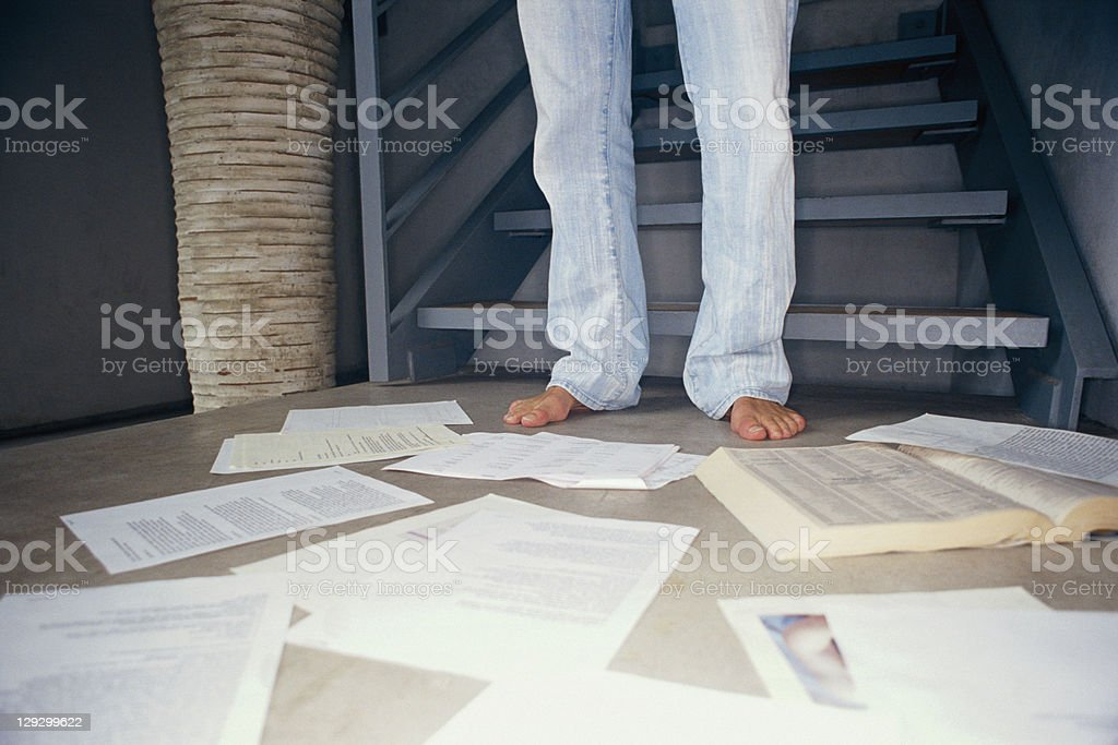 Man surrounded by papers on floor stock photo