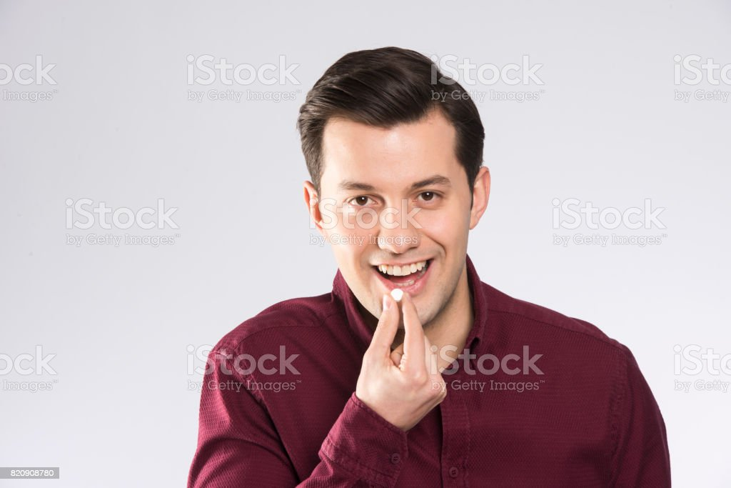 A man swallowing a pill with a smile on his face stock photo