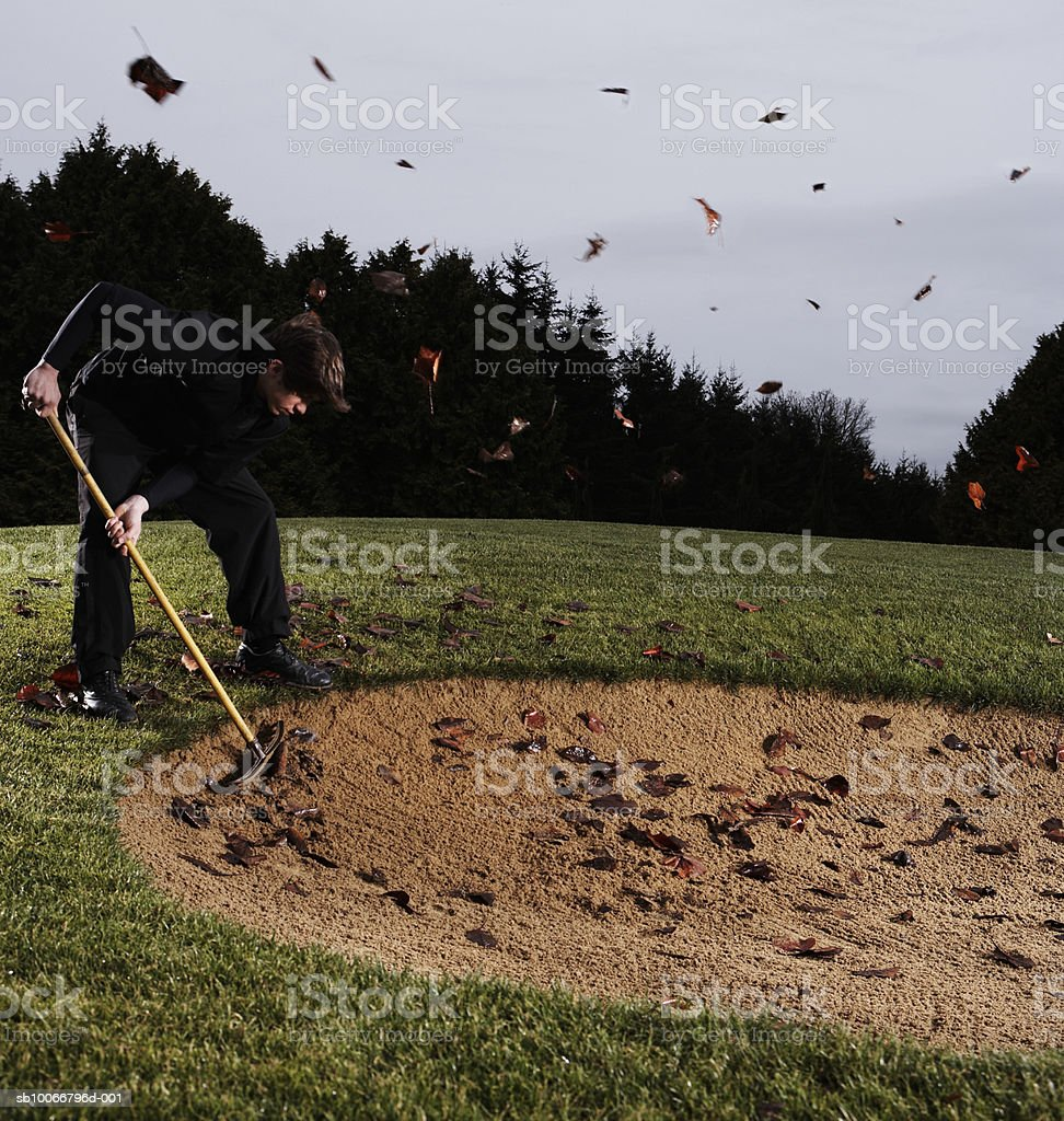 Man sweeping golf course with broom, side view royalty-free stock photo