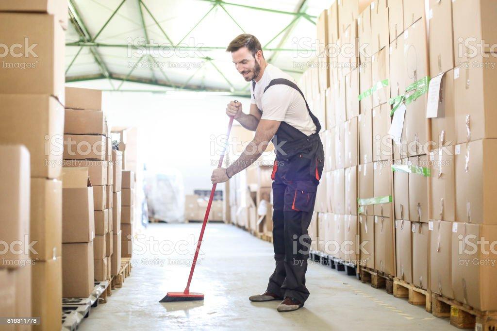 Man sweeping the warehouse floor stock photo