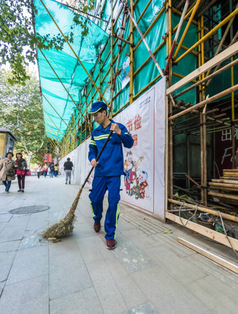 Man sweeps sidewalk with an old broom in Shanghai stock photo