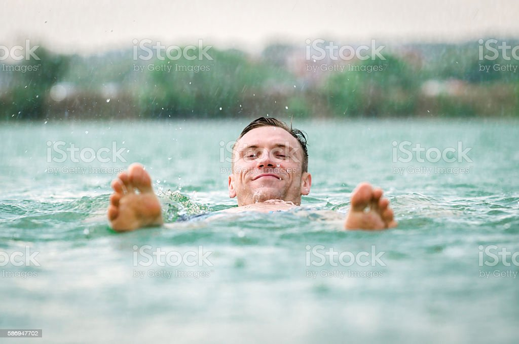 Man swimming in lake under the rain in thunderstorm stock photo