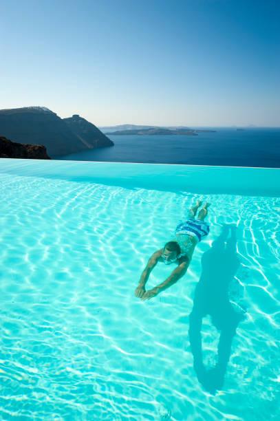 Man Swimming Underwater Infinity Pool Santorini stock photo
