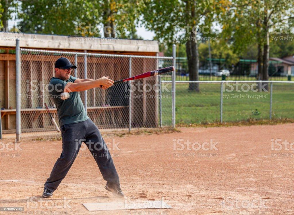 A man swinging a baseball bat stock photo