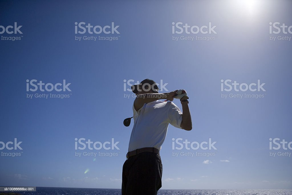 Man swinging golf club, low angle view royalty-free stock photo