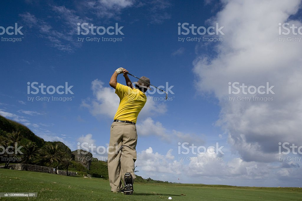 Man swinging golf club, rear view royalty-free stock photo