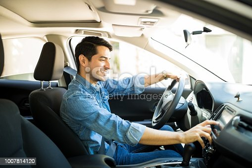 istock Man switching radio station while driving 1007814120