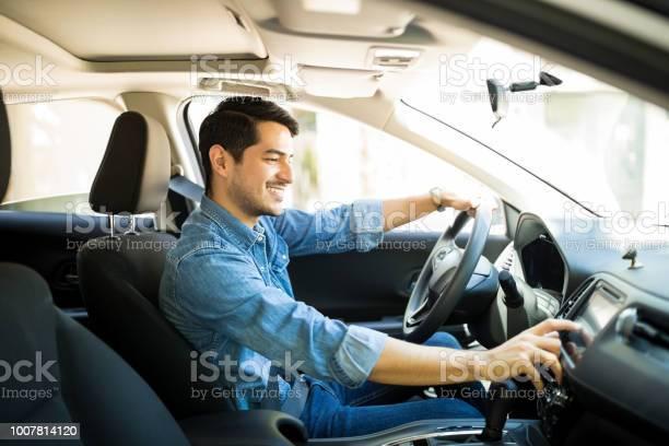 Man switching radio station while driving picture id1007814120?b=1&k=6&m=1007814120&s=612x612&h=n9se4b by 8lu9rldcnprezxy2xpxfe zfx2 lzp2ai=