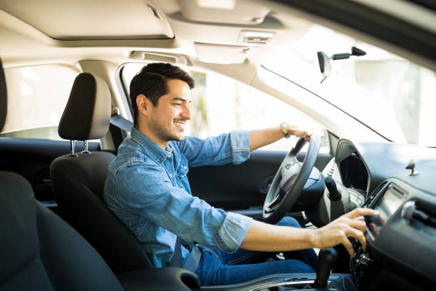 Man switching radio station while driving Handsome young man in denim shirt pressing touchscreen on car multimedia panel, switching shifting radio station. car stock pictures, royalty-free photos & images