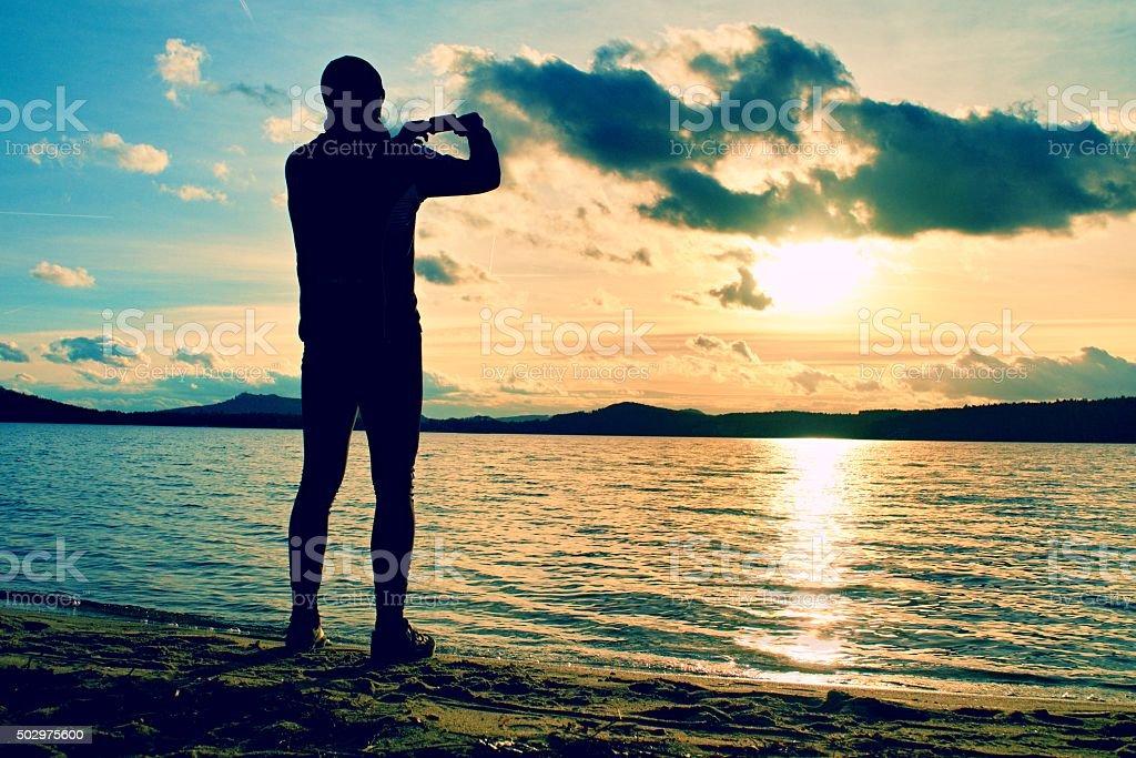 Mann nehmen Foto von den Sonnenuntergang mit Handy. Herbst-Küste – Foto