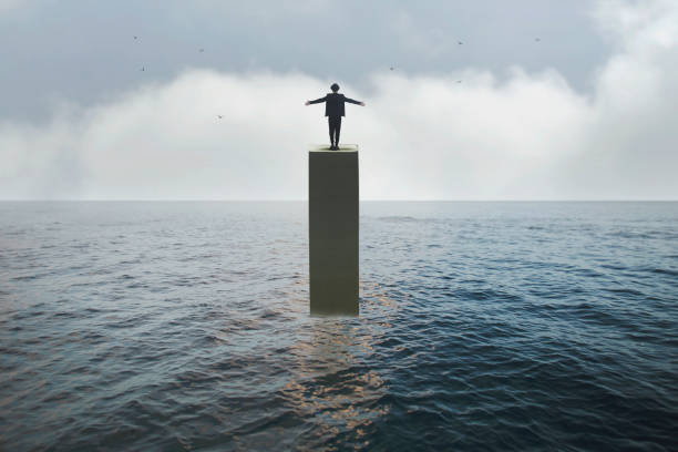 man takes a breath on a tower in the middle of the ocean, concept of freedom and success stock photo